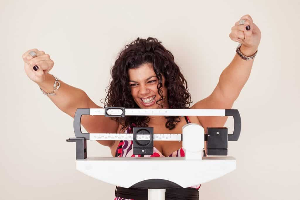 Happy woman celebrating her weight loss on a medical weight scale.