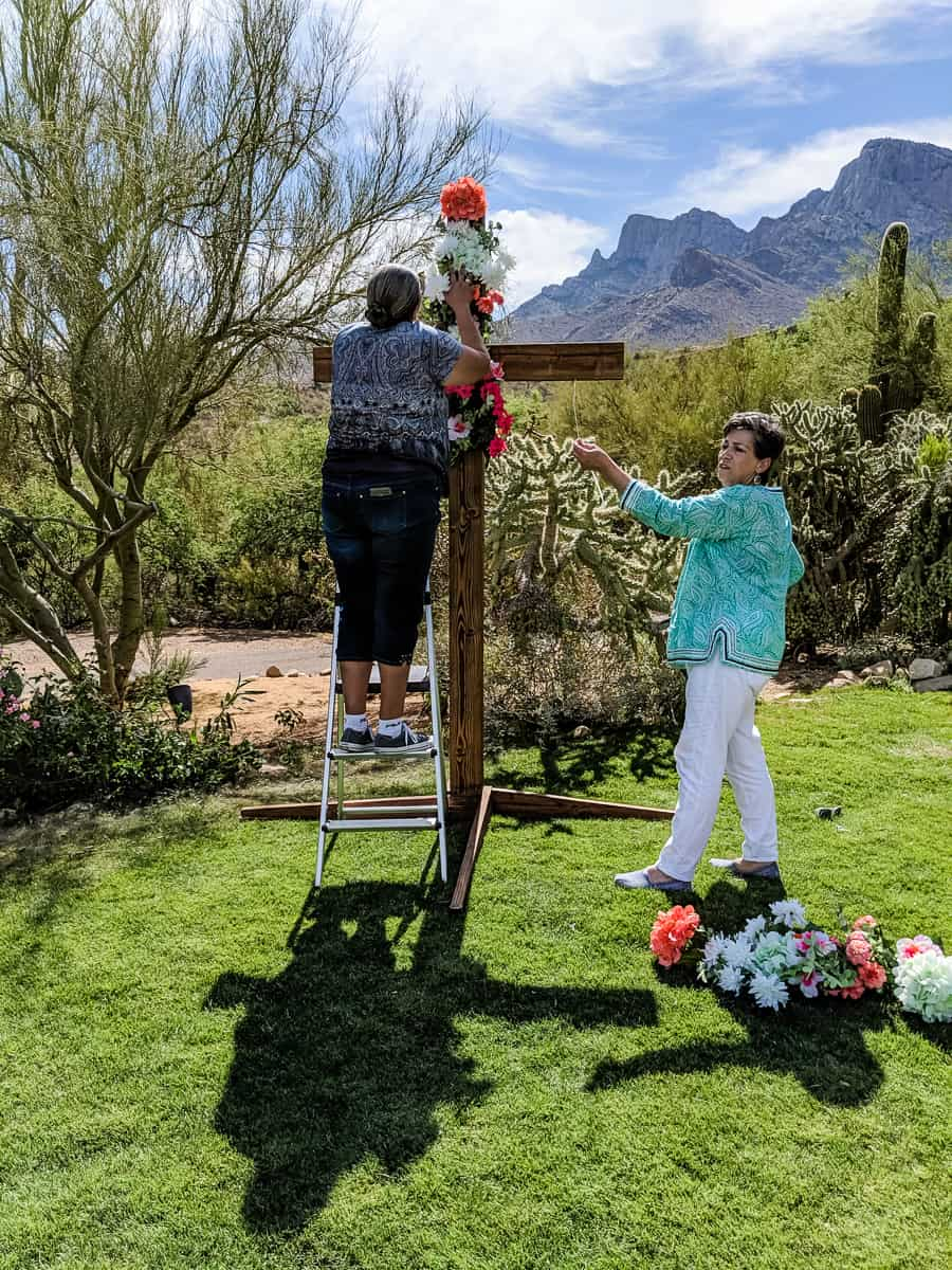 Florists decorating floral wedding cross with silk flowers.