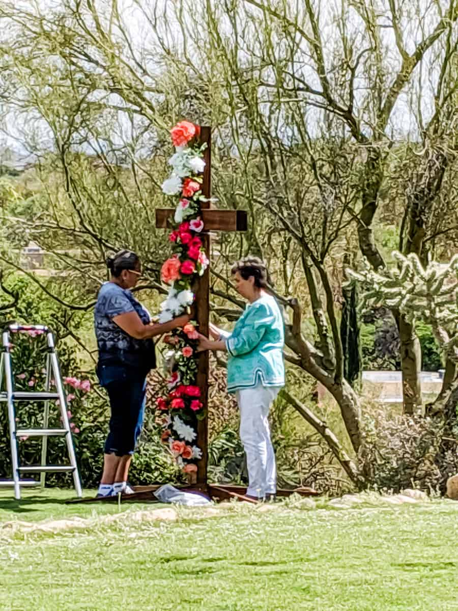Florists decorating floral wedding cross