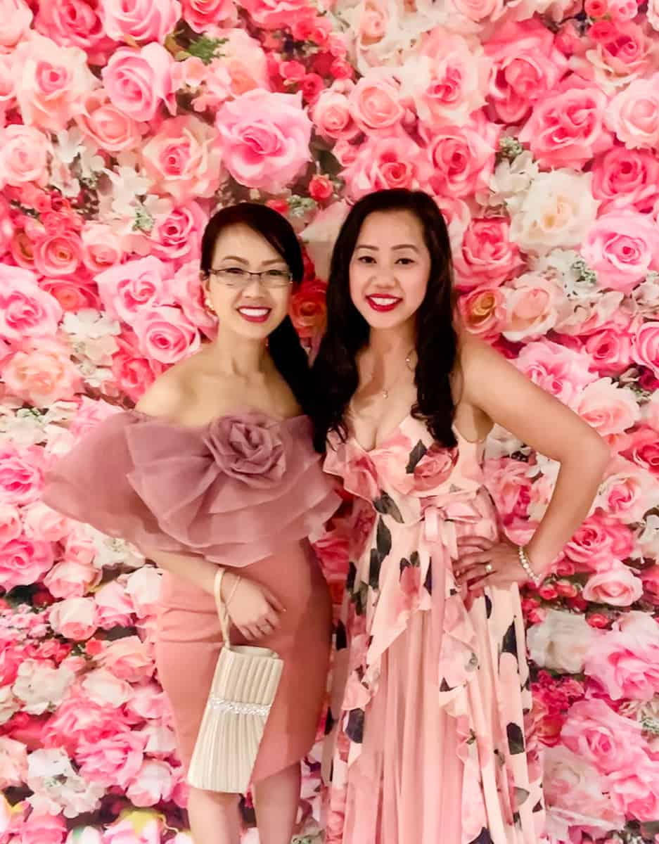 Two women in front of pink floral backdrop