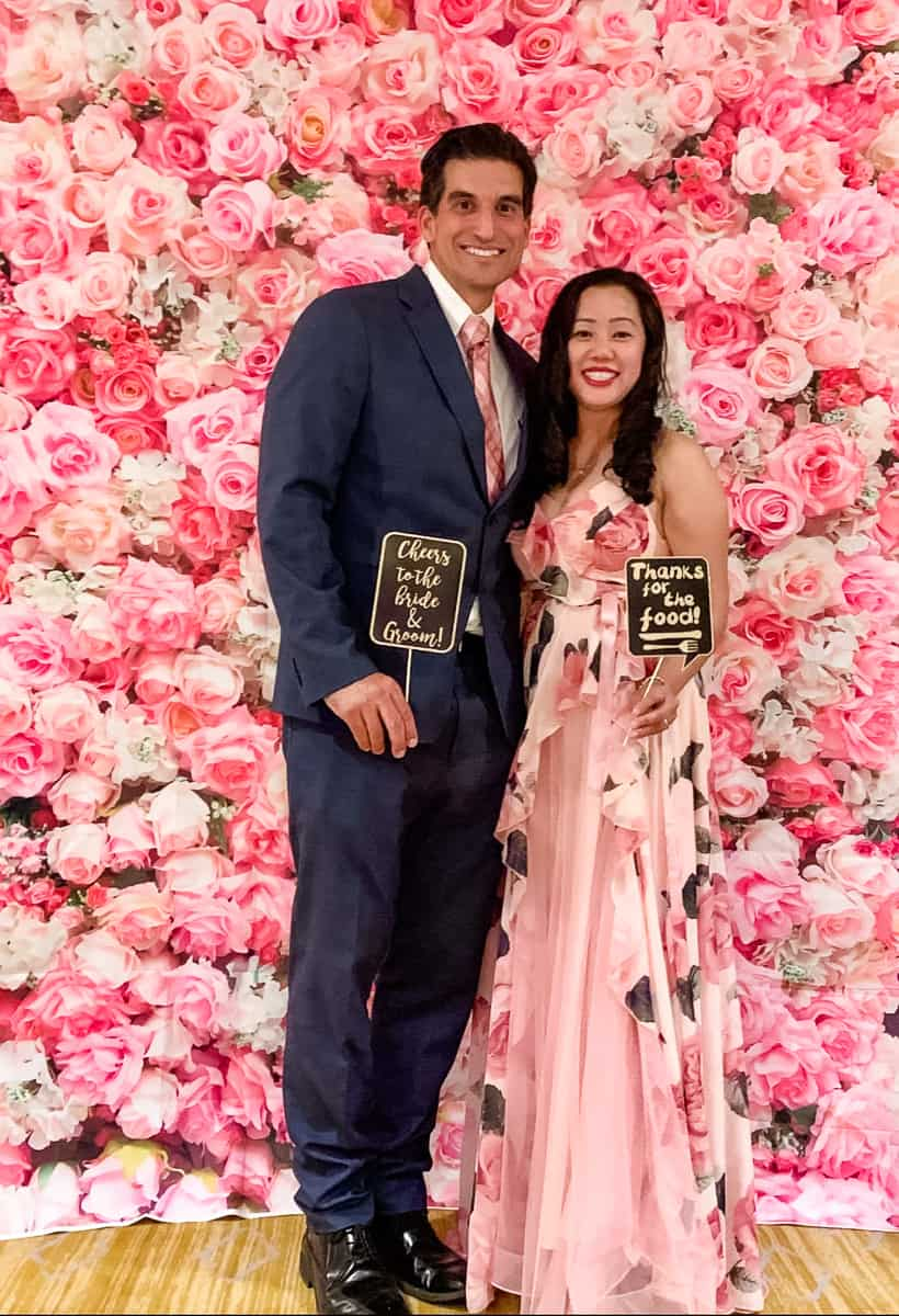 Husband and wife in front of floral photo backdrop selfie station