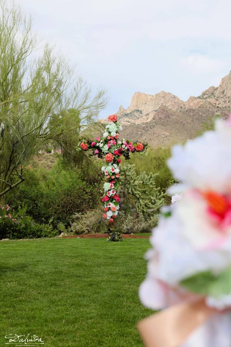 Floral ceremony cross with mountain backdrop at Hilton El Conquistador