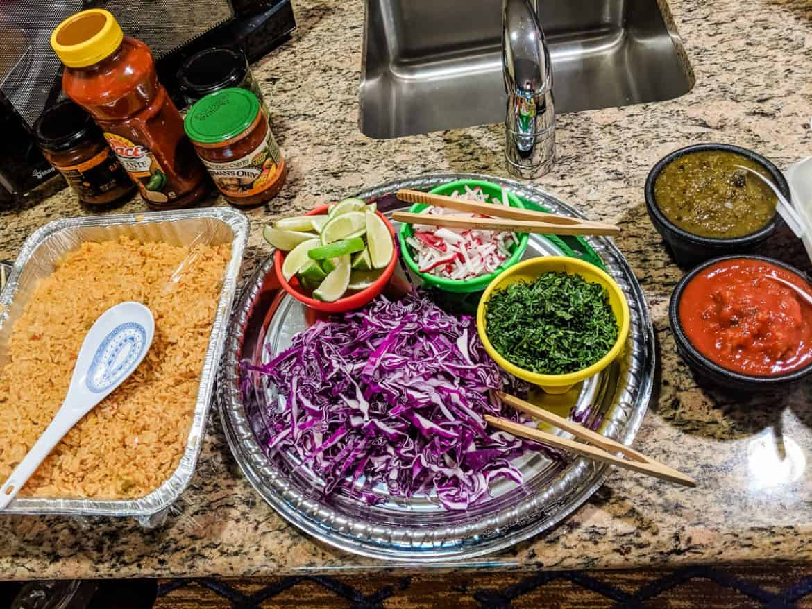 Build your own taco bar with purple cabbage, limes, cilantro, salsa, rice and radishes.